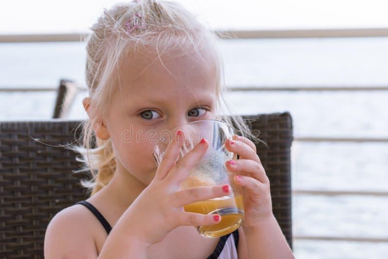 Питье маленькой девочки сок стоковые изображения
