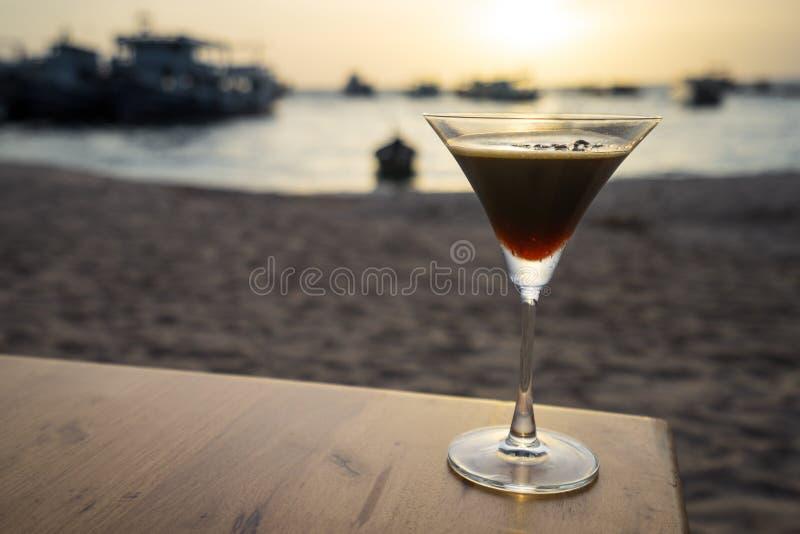 Питье на пляже захода солнца стоковые изображения rf