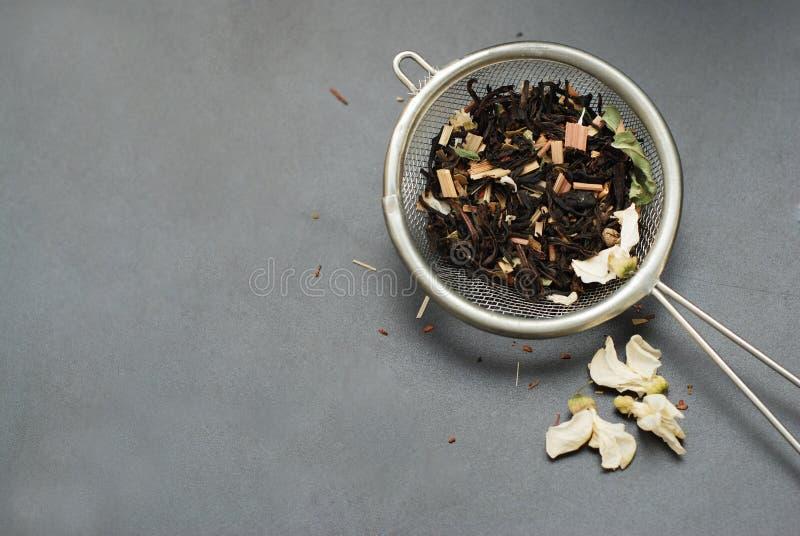 Питье травяного чая Acaccia здоровое в шаре и сетка над черной предпосылкой копируют космос Здоровое питье, холодность стоковая фотография