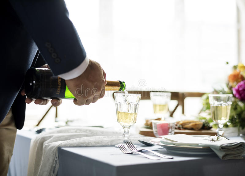 Питье Шампани руки лить заполняя к стеклам стоковая фотография