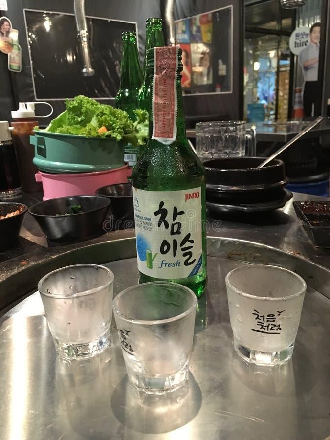 Питье Soju Кореи в зеленой бутылке стоковое фото rf