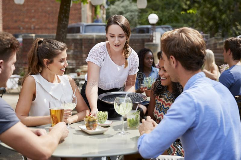 Пить сервировки официантки к группе в составе друзья сидя на таблице в саде паба наслаждаясь питьем совместно стоковые изображения rf