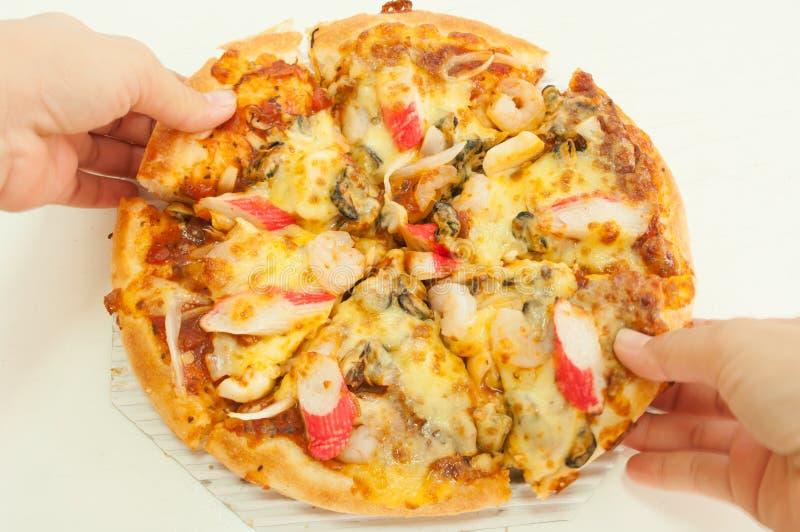 Пицца в руке в белой предпосылке стоковые изображения rf