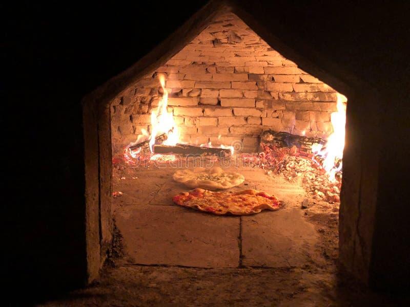 Пицца 2 в старой деревянной печи стоковые изображения rf