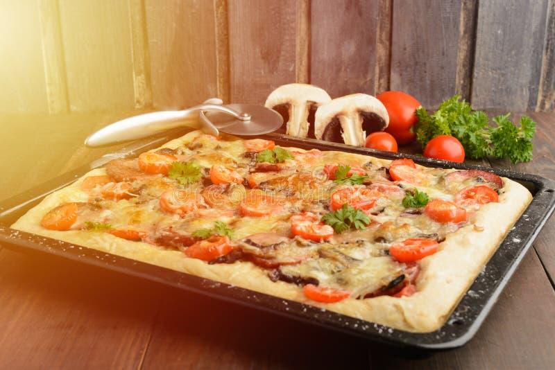 Пицца дома с некоторыми ингридиентами и специальным ножом над woode стоковые фотографии rf
