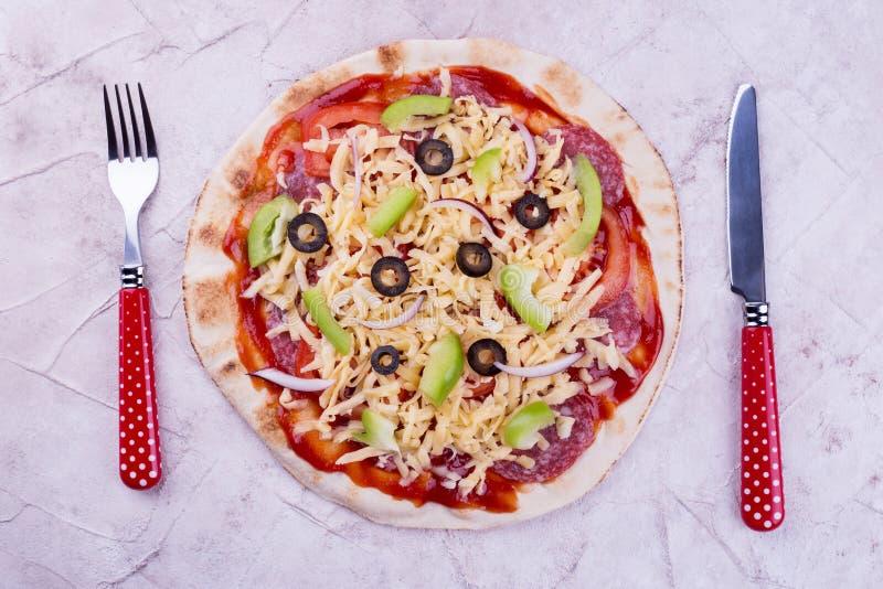 Пицца и красный столовый прибор стоковое изображение