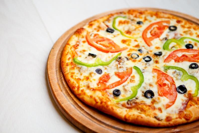 Пицца на деревянной плите стоковые фото