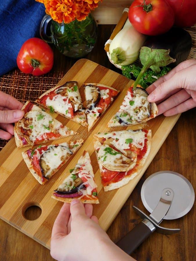 Пицца отрезанная в этапы принимается с руками 3 людей стоковое изображение rf