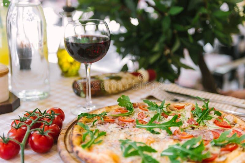 Пицца с бокалом вина, на, который служат таблице стоковая фотография rf