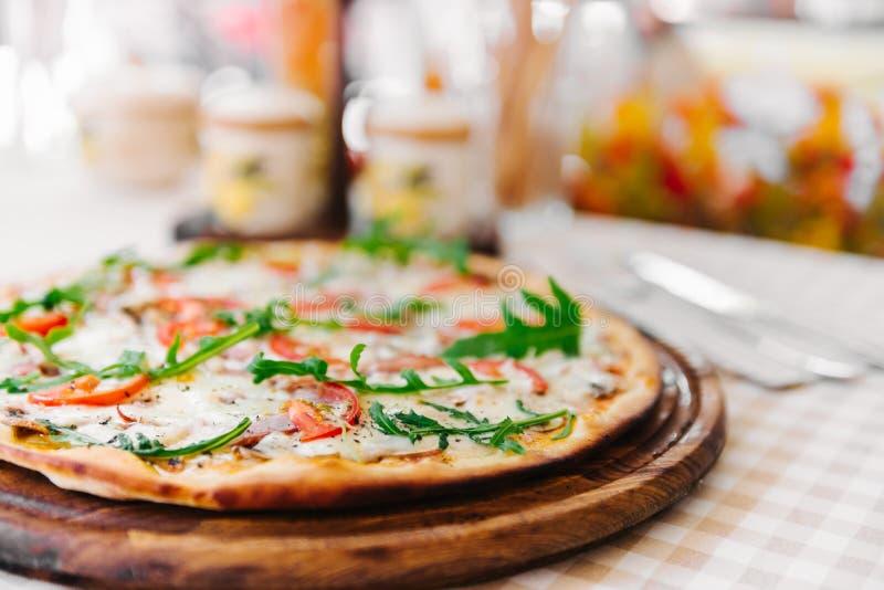 Пицца с сыром, томатом и мясом, на, который служат таблице стоковая фотография
