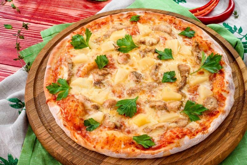 Пицца с цыпленком и ананас на круглой деревянной доске на красной деревянной предпосылке стоковые фото