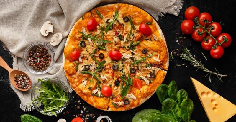 Пицца украшенная с салатом ракеты и томатами вишни стоковая фотография