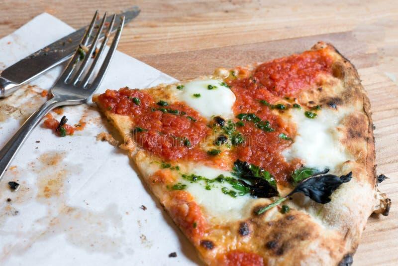 Пицца fo части взгляда сверху с томатами, моццареллой, базиликом и столовым прибором на, который служат деревянной таблице рестор стоковое изображение rf