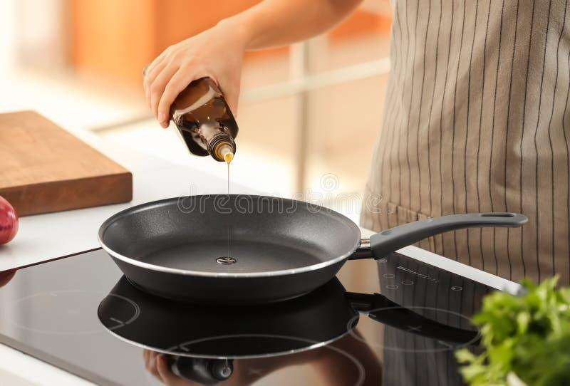 Пищевое масло женщины лить от бутылки в сковороду стоковое изображение rf