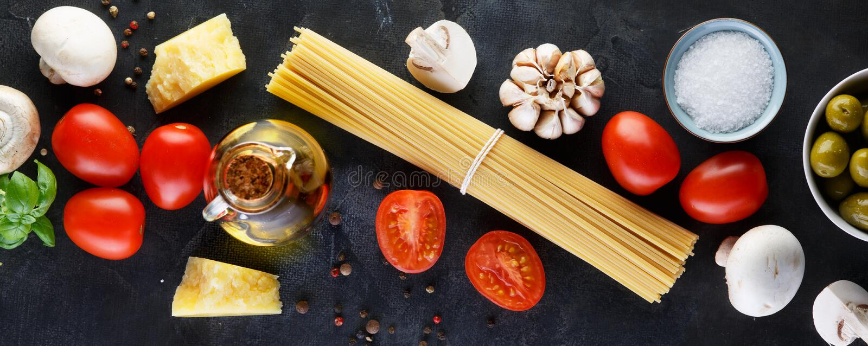 Пищевые ингредиенты для итальянских макаронных изделий, спагетти на черной каменной предпосылке шифера r стоковое изображение rf