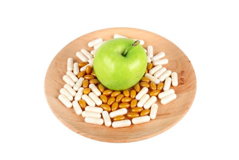 Пилюльки на деревянной плите и яблоке изолированном на белизне стоковое фото