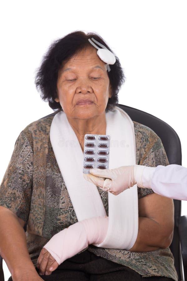 Пилюльки с старшей женщиной раненой стоковое изображение rf