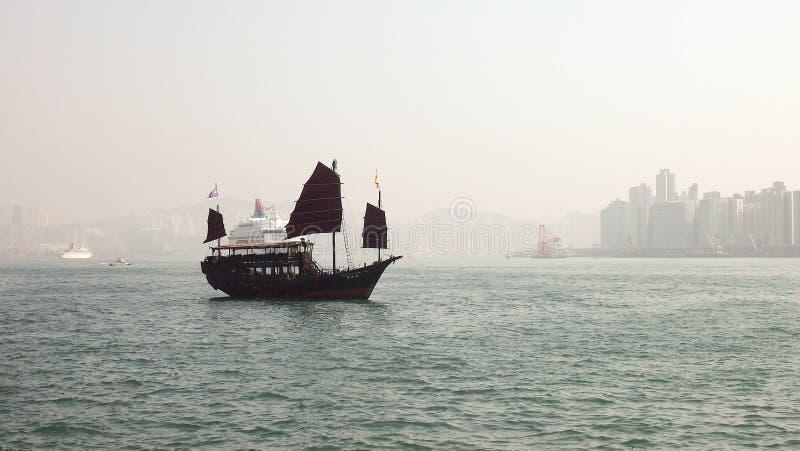 Плавание корабля гавани Гонконга деревянное с горизонтом здания стоковая фотография