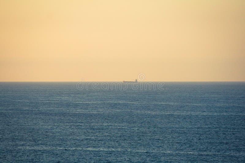 Плавание корабля топливозаправщика через море на заходе солнца стоковые изображения