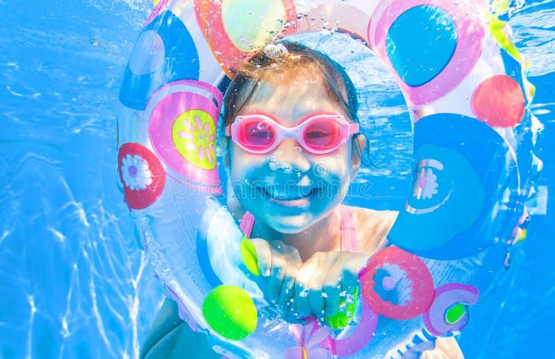 Плавание маленькой девочки в бассейне стоковые изображения rf
