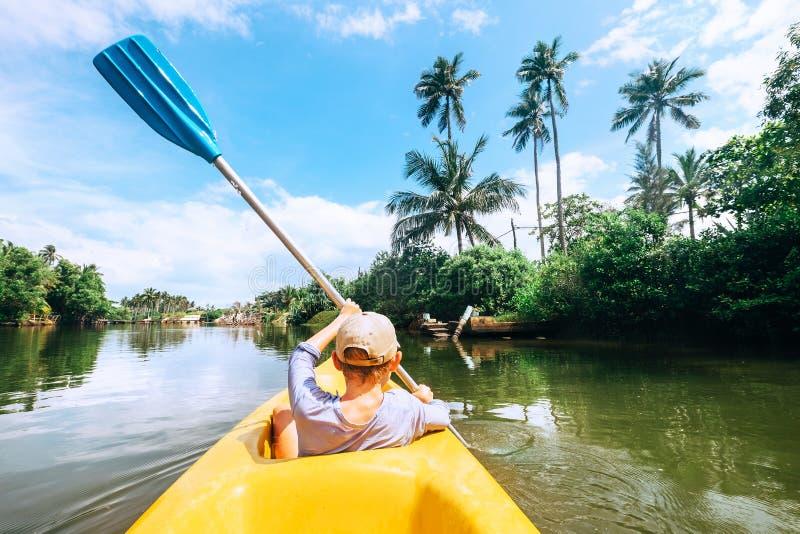 Плавание мальчика в шлюпке каное на тропической лагуне стоковое изображение rf