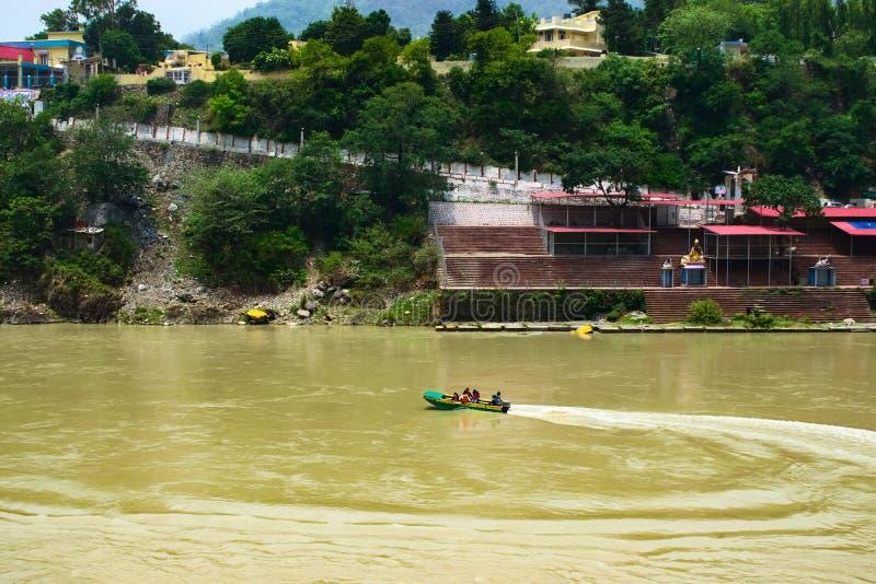 Плавание шлюпки в реке в Священном городе Rishikesh в назначении Индии очень популярном туристском и красивом естественном surrou стоковые фото