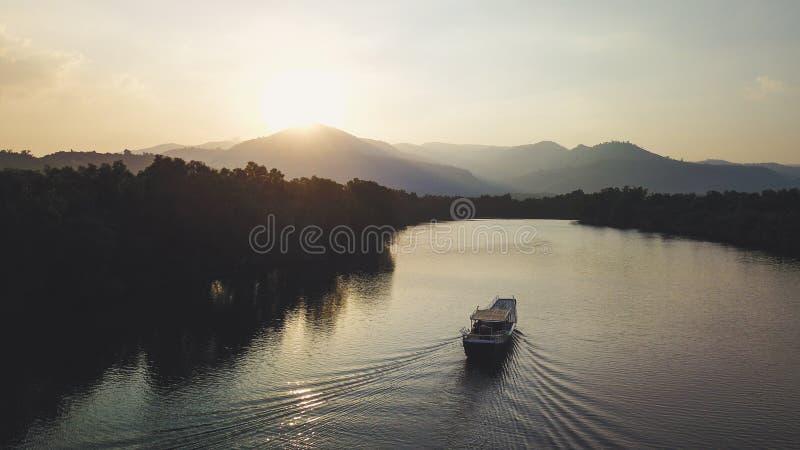 Плавание шлюпки к заходу солнца перед горой Ридж Съемка трутня стоковая фотография rf