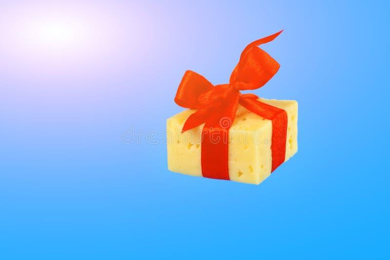 Плавать в подарок воздуха сыра связанный с красной лентой на крысах Нового Года на голубой предпосылке стоковое фото