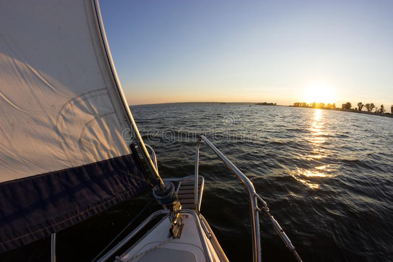 Плавать на заходе солнца Взгляд от палубы яхты к смычку и ветрилам стоковое фото