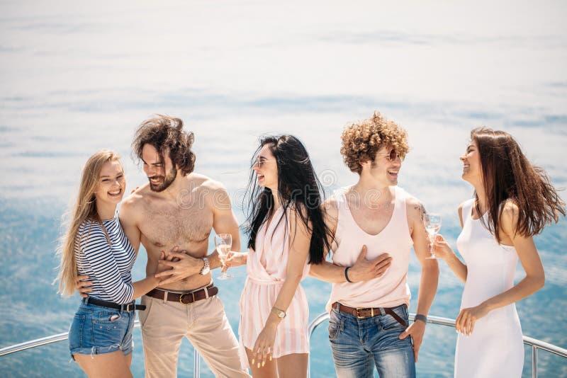 Плавать партия при молодые люди имея партию шлюпки, танцуя на смычке палубы яхты стоковая фотография rf