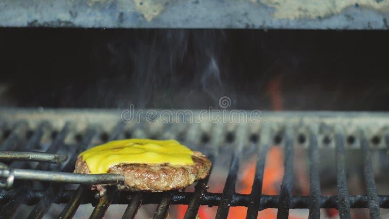Плавя чеддер на Cheeseburger Жарить бургер на BBQ стоковое фото rf