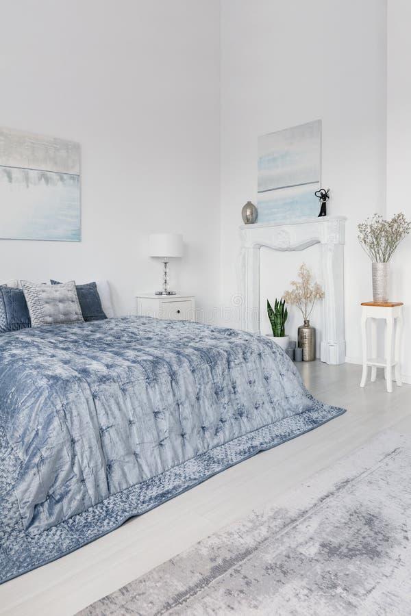 Плакаты и заводы в белой простой спальне внутренней при включении голубые кровать и лампа шкаф Реальное фото стоковое изображение rf