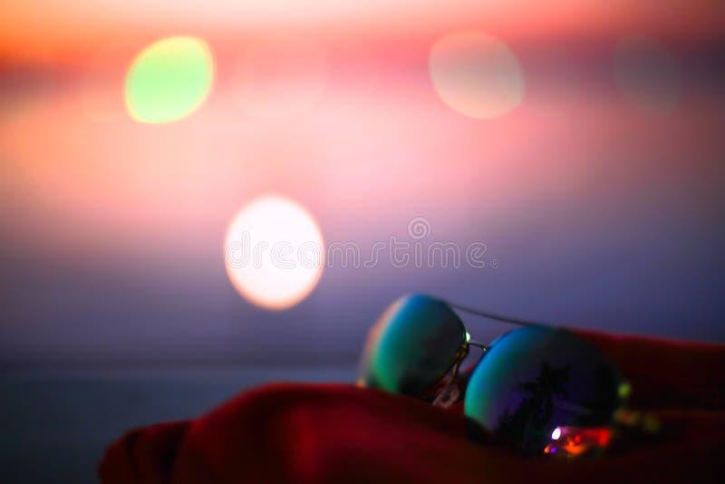 Плакат лета с солнечными очками, ладонями и влияниями bokeh Запачканная предпосылка пляжа захода солнца стоковые изображения