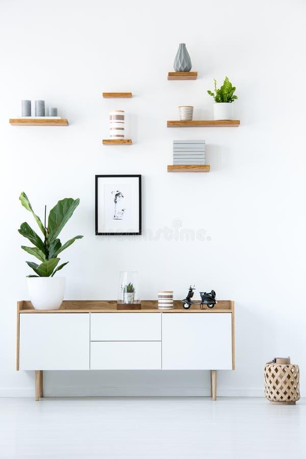 Плакат над деревянным кухонным шкафом с заводом в минимальном белом apartme стоковая фотография rf