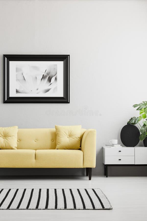 Плакат над желтой софой в минимальном сером интерьере живущей комнаты с половиком и кухонным шкафом Реальное фото стоковое фото rf