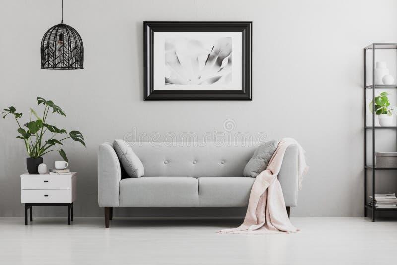 Плакат над серой софой с розовым одеялом в интерьере живущей комнаты стоковая фотография rf