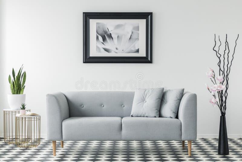 Плакат над серым креслом с подушками в минимальном интерьере живущей комнаты с заводом на таблице золота Реальное фото стоковая фотография