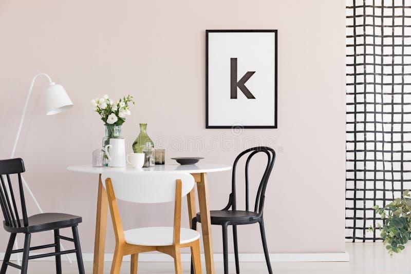 Плакат на пастельной розовой стене изощренной столовой внутренней с круглым столом стоковая фотография rf