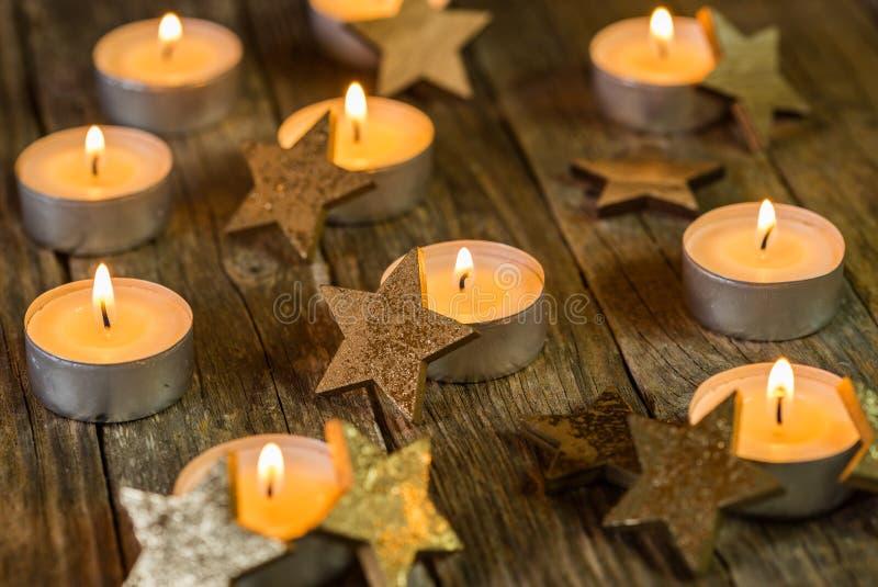 Пламена свечи пришествия и рождества с золотым украшением звезды на деревянном столе стоковые фотографии rf