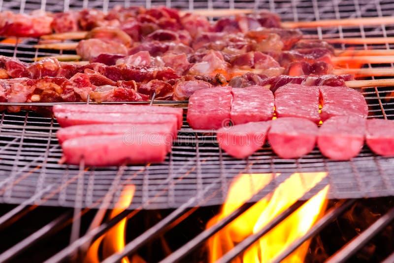 Пламя под сосиской жаркого на крупном плане плиты барбекю стоковое фото