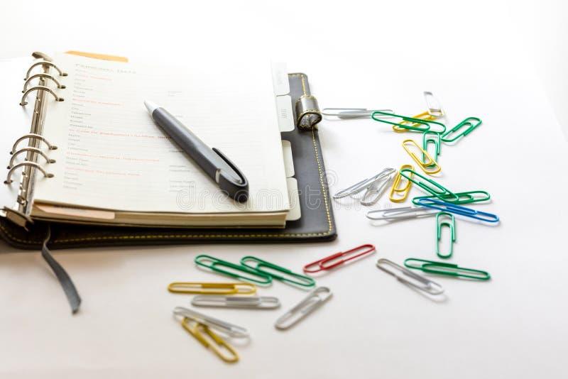 Плановик с черной ручкой раскрытой на белой предпосылке стоковые фотографии rf