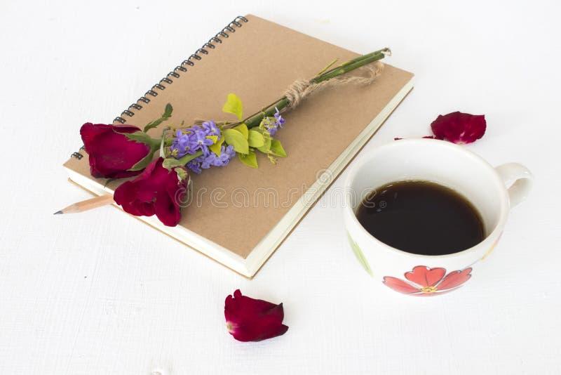Плановик тетради для работы дела с горячими эспрессо и красной розой кофе стоковые изображения rf