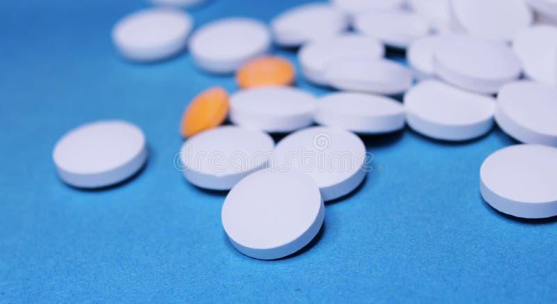 Планшеты медицинского круга белые и оранжевые, крупный план витаминов кальция на голубой предпосылке Таблетки стоковая фотография