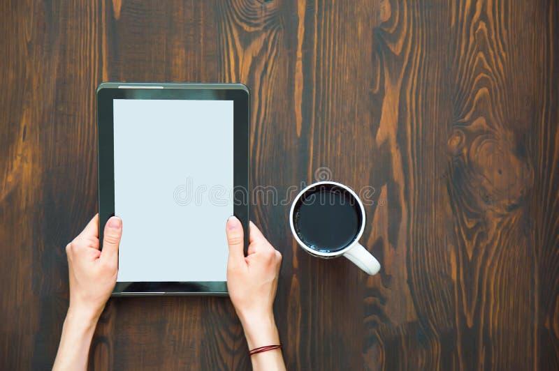 Планшет в руках на поле и чашке кофе рядом с стоковое фото