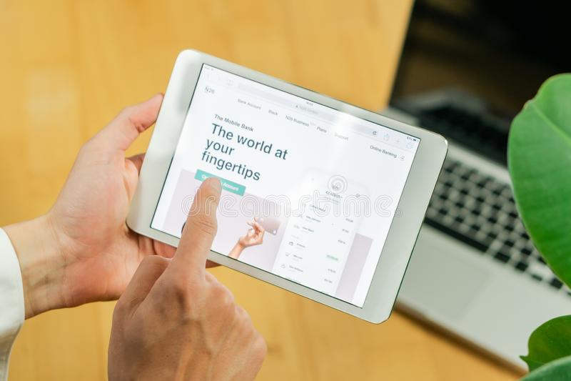 Планшет компьютера удерживания бизнесмена с вебсайтом раскрытого банка n26 на столе офиса стоковая фотография