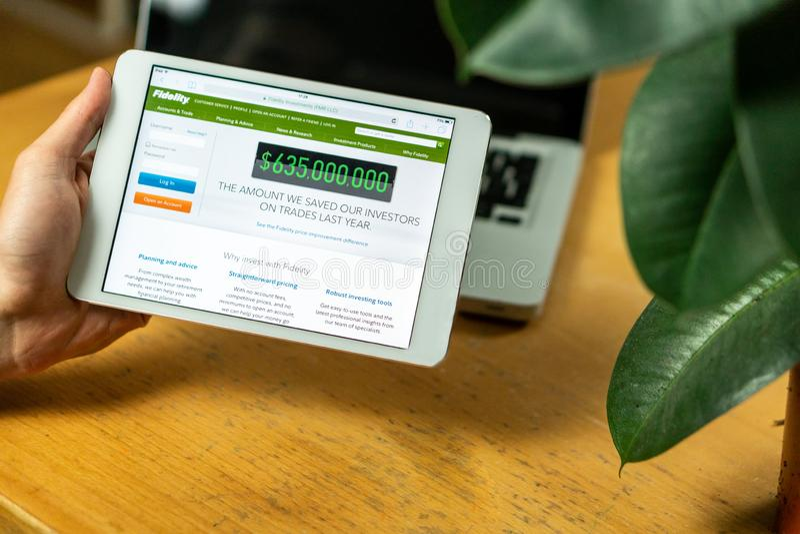 Планшет компьютера удерживания бизнесмена с раскрытым вебсайтом Fidelity на столе офиса стоковые фото