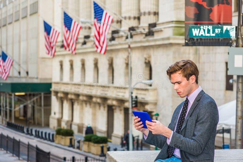 Планшет чтения молодого человека на Уолл-Стрите в Нью-Йорке стоковая фотография rf