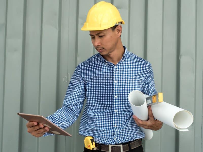 План и удерживание чертежа конструкции светокопировальной бумаги владением инженера планшет, архитектор работая в офисе, инструме стоковые изображения rf