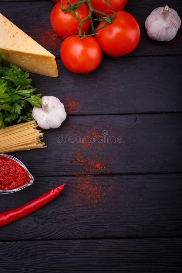 План продуктов на таблице спагетти, томата вишни, петрушки, трудного сыра, горячего перца и чеснока indoors стоковое изображение