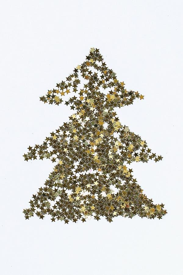 План рождества Золотой confetti в форме звезд сложенных в форме рождественской елки стоковые изображения
